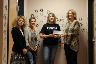 TVEC Public Relations Representative Kari Wilmeth, right, presents a grant check to Living Alternatives representatives Cheryle McCann, Renee Landers and Rachel Chapman.