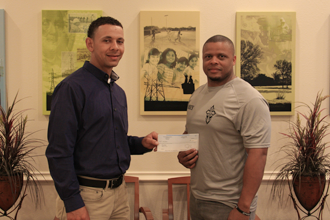 TVEC Energy Management Advisor Chris Walker, left, presents a grant check to Corey Rodriguez from Men Unleashed.